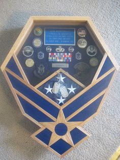 Visit us on Facebook at www.facebook.com/FullMedalJacket and give us a like! Now available with navy blue inlays! This Air Force Shadow Box is handcrafted from solid oak and will protect and display your medals, patches, rank, coins, and flag from your many years of service. Background fabric is blue suede cloth. Glass is double strength. Optional addition of glass etching of rank insignia over area where flag is displayed is available. If you desire a design etched over the flag area…