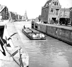 1940's. A view of the Oudeschans with Montelbaanstoren in Amsterdam. In the foreground the Sint Antoniesluis. On the right the Goslerhuis and Joden Houttuinen. The Oudeschans canal is an extension of the Zwanenburgwal and runs from the St. Antoniesluis (sluice) to the Oosterdok, that is connected to the river Het IJ. The canal forms the eastern shore of Uilenburg on the border of de Lastage neighborhood. Photo De Arbeiderpers. #amsterdam #1940 #Oudeschans