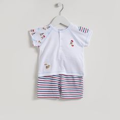 A lovely Bermuda short set for baby boy or toddler from Kissy Kissy. Made from 100% Peruvian pima cotton for softness and comfort. This outfit has pirate and pirate ship print and an embroidered motif on the top left hand side of the shirt. Stripy pocket on left sleeve. Red and blue stripes on shorts. Elasticated waist …