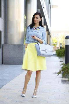 Shop this look on Lookastic:  http://lookastic.com/women/looks/denim-shirt-full-skirt-pumps-satchel-bag-necklace-ring/11339  — Silver Leather Pumps  — Multi colored Necklace  — Multi colored Ring  — Light Blue Denim Shirt  — Light Blue Leather Satchel Bag  — Yellow Full Skirt