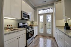 Galley kitchen, patio doors, hardwood floors, white cabinets, stone counters