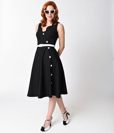 We bet your buttons you'll turn heads, dears! Nettie is a 1950s retro frock of soft black stretch that provides comfort and support for a perfect figure flattering cut. A stylish scalloped neckline with a sleeveless bodice nips in to the waistline and  w