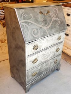 Turn some old furniture pieces into something really cool. Turn an old secretary desk into a stylish piece of decor with metallic finish that is quite trendy. After some screwing and gluing she covered them with primer, spray paint with metallic paint and cover with mix of metallic paint, black acrylic and water. Hand paint some details and add original antique hardware.
