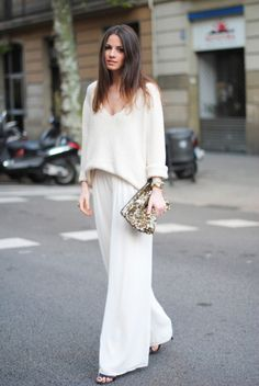 25 Winter White Outfits to Try - wide leg trousers worn with a v-neck sweater + gold sequin clutch