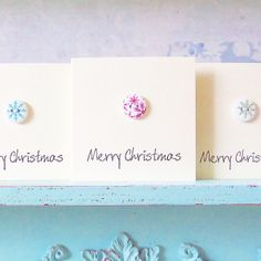 """Christmas Snowflake Cards - Pack of five small cards, each with a different snowflake button design.   (One pack available, but happy to make more if needed. Please request a custom order. Able to dispatch in 1 - 2 days).  These cute little cards have been decorated with a wooden button, each stitched directly onto the card.  Inside has been left blank for your own message. Each card measures approx : 3"""" by 3"""" and comes with an envelope to match.  Listing is for one pack only.  **Please be…"""