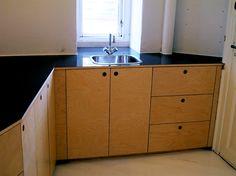 Køkkenet er finér af birk med bordplade af sort højglans ridsefri laminat. Køkkenet har indenvendige skuffer i dele af skabene.