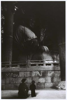 Adult and child sit beside a giant Buddhist statue, Nara, Japan