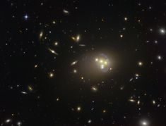A Hubble Space Telescope image of galaxy cluster Abell 3827, where dark matter may have been observed interacting with itself during a galaxy collision.<br />