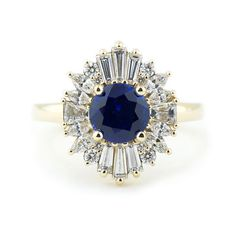 """A vibrant blue sapphire engagement ring inspired by traditional art deco """"ballerina ring"""" designs. This Gatsby-esque halo uses a combination of baguette, marquise, and round diamonds in descending sizes to create a bursting star effect. 14k yellow gold adds an overall warmth to the design, while the deep blue sapphire and white diamond color palette is reminiscent of Princess Diana's engagement ring. This art deco sapphire ring was commissioned and made from scratch…"""