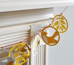 Laser cut garland. << I like the concept of a string of identically-shaped/sized medallions with various internal motifs