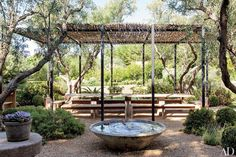 At their residence in Malibu, California, actor Patrick Dempsey and his wife, Jillian, enlisted Shrader Design to create this outdoor dining space, which is shaded by a metal-framed wicker canopy.