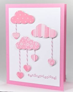 This pinkalicious card will totally welcome your new baby bundle! The clouds and dangling hearts have been attached to craft board to make them thicker, and they really pop from the card. The hearts are dangling from pink/white baker's twine.