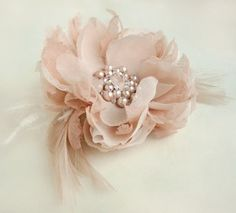 This blush peony hair clip is made out of 3 different silk fabrics to create a multi dimensional flower.Beaded with genuine freshwater pearls and crystals it has personality to spare. Paired with blush and ivory feathers for an accent.Measures about 3 1/2 inches in diameter (8-9 cm).