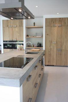Progetto cucina in muratura moderna - isola centrale con top in cemento e sportelli in rovere con grandi maniglie in acciaio inox