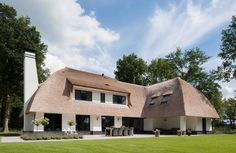 Strakke wit gestucte riet gedekte villa met zwarte kozijnen - 01 Architecten - Ontworpen door Dennis Kemper tijdens de periode dat hij bij EVE-architecten werkte.