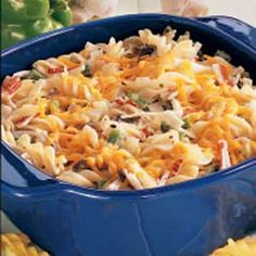 PASTA CRAB CASSEROLE  8 ounces uncooked spiral pasta  2 large onions, chopped  1/2 pound fresh mushrooms, sliced  1/2 cup chopped green pepper  1/2 cup butter  2 garlic cloves, minced  2 packages (8 ounces each) imitation crabmeat, chopped  1/2 cup sour cream  2 teaspoons salt  1-1/2 teaspoon dried basil  1-1/2 cup (6 ounces) shredded cheddar cheese