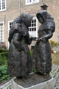 Breda - Begijnhof (kruidentuin). Beeld van 2 bronzen begijnen (Hans Bayens/1971), gemaakt t.g.v. het zilveren priesterjubileum van pastoor Ooms. Hij was de laatste pastoor van het begijnhof, waar vanaf 1246 altijd een pastoor werkzaam was geweest. De laatste begijn van Nederland, zuster Frijters, overleed hier overigens op 13/4/1990. Foto: G.J. Koppenaal,30/7/2015.