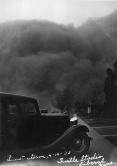A photograph showing a dust storm in Liberal, Kansas. An automobile is in the foreground.    Date: 1935