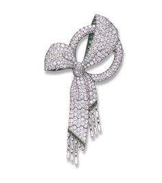 AN ART DECO DIAMOND AND EMERALD BROOCH Designed as a pavé-set diamond circle brooch, enhanced by a sculpted pavé-set diamond bow, with calibré-cut emerald detail, to the articulated ribbon, terminating in baguette and single-cut diamond fringe, mounted in platinum, (two diamond drops deficient), circa 1930