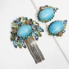 This gorgeous vintage brooch and earrings set looks like the very essence of spring! Large cabochons of clouded robin's-egg blue are the centers of these lovely pieces. On the brooch, the blue cab is framed by marquise rhinestones in pale green, blue a...