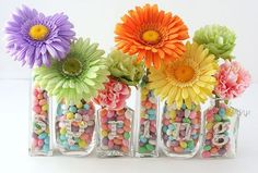 Edible table center piece idea. I think three jars of assorted sizes filled with jellybeans and a bright flower would make a funky table center piece. Jars could be from empty sauce bottles, jars etc and you could add a tag with a poem explaining that they are welcome to eat the jelly beans.