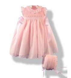 Faldón infantil confeccionado en batista rosa bordado a mano en punto Smock o nido de abeja rematado con festones también bordados a mano,con capota a juego de moda infantil.