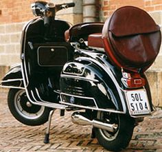 vintage black vespa with brown leather seats