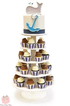 This cupcake tower and cake topper was created for a whale themed baby shower in Boonton, NJ last weekend. The top tier includes a cute gray whale spouting turquoise, navy and white water from his blowhole. The front of the topper includes an anchor and rope to round out the nautical/whate theme.