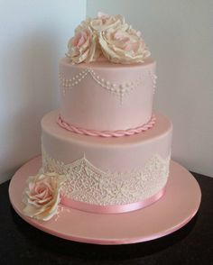 Beautiful pale pink wedding cake with piped lace and pink vintage roses.