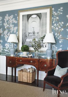The Gracie wallpaper was hand-painted, panel by panel, right in the dining room. To counteract the classicism created by the pairing of the antique sideboard with the wallcovering's chinoiserie motif, designer Susan Bednar Long hung a contemporary Matthew Pillsbury photograph.