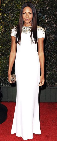 Naomie Harris hit the Governors Awards in a stunning, cap-sleeved, white Burberry gown, adorned by metallic hardware tracing the sleeves and her exposed back.