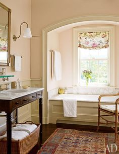 The master bath's alcove frames a Waterworks tub; the sconce is by Ann-Morris Antiques, the window-shade fabric is by Robert Kime, and the sink stand was designed by Schafer.