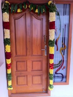 Nilai maalai/flower garland for decorating main door of the house is considered auspicious.  Notice those mango leaves on top. Mango leaves toran is sacred