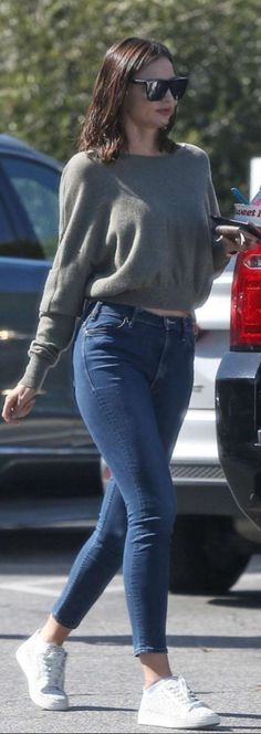 Who made  Miranda Kerr's black sunglasses, blue skinny jeans, brown print wallet, gold jewelry, and white sneakers?