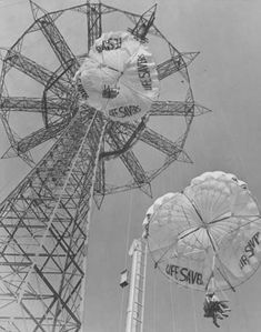 """1939 NY World's Fair. """"Parachute Drop. Eleven gaily colored captive parachutes, each seating two passengers are hoisted by steel cables to the top of the 250 foot tower, where an automatic release drops parachute and passengers into the thin air, giving the sensation of """"bailing"""" out from a winging plane. """""""