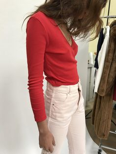 red ribbled wrap top and blush (or off white?) jeans.