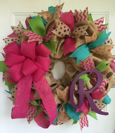 This is a cute Spring/Summer burlap wreath measuring approximately 23. High quality tight weave burlap is base of wreath. Full of colored jute ribbons! Left side is adorned with bright pink bow. Birch wood Initial of your choice painted plum purple on the right. Initial can be painted your choice of color. Initial will be purple as pictured unless you specify otherwise. Place wreath in well protected area if using outdoors. If you like this wreath but would like to change bow color ... P...