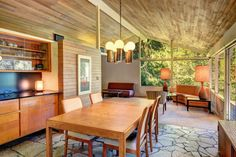 fab open plan living mid century home. Loving the slate floors, large windows looking into the tree tops and brass chandelier light