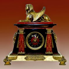 French Antique Egyptian Revival mantle clock made of bronze and marble adorned with winged sphinx ~ 19th century