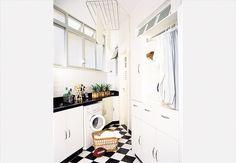A unidade com o estilo do apartamento se dá com o quadriculado preto-e-branco de cerâmica no piso. Sob o tampo de trabalho, um armário claro de fórmica guarda os utensílios e produtos de limpeza. Ao fundo, uma porta do armário ocupa o canto  Arquivo / Casa e Jardim