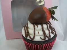 Chocolate cupcake topped with vanilla buttercreme, chocolate drizzle, and a chocolate covered strawberry.