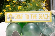 """This """"Gone To The Beach"""" sign in very coastal colors has been hand carved and painted. Comes in Yellow, Blue or Red. Measures 12"""" long x 4"""" tall."""
