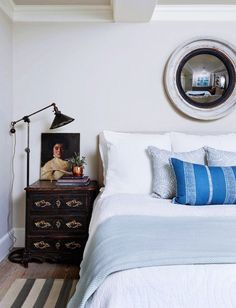 Blue bedroom with rustic accents and porthole mirror.