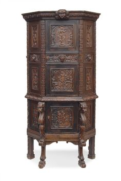 A small Historismus cabinet    Gdansk, c. 1860 /70. Wood, carved, darkened. Six-egded cabinet, bottom and top each with 1 door. Carvings with minotaurus and nymph, Justitia, Victoria and with monkeys, lions, grapes and flowers. Partly small traces of age. H. 186 cm, w. 100 cm, d. 59 cm.