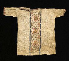 A COPTIC TEXTILE TUNIC FOR A CHILD 6TH CENTURY A.D. The central panel with red, yellow and green embroidered foliate motifs bordered by two white and dark blue bands, the collar and sleeves edged with red and white bands 15 in. (38 cm.) high