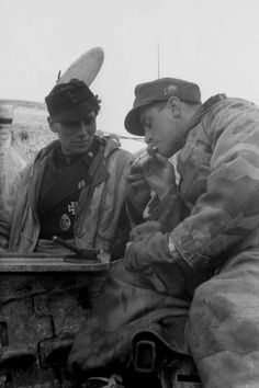 A decorated soldier of a Panzer IV tanklight a cigarette to aGebirgsjäger Kameradduring a rest period. Army Group South, Ukraine, December 1943.