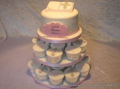Baptism cake and cupcake tower. The top cake is a simple round cake with bible…