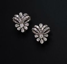 A PAIR OF DIAMOND EAR CLIPS Each designed as circular and baguette-cut diamond stylized ribbons, gathered by a circular and pear-shaped diamond demi-floret motif, mounted in platinum. Would guess circa Diamond Earing, Diamond Jewelry, Gold Jewelry, Vintage Jewelry, Fine Jewelry, Gold Bracelets, Diamond Stud, Cartier Jewelry, Solitaire Diamond