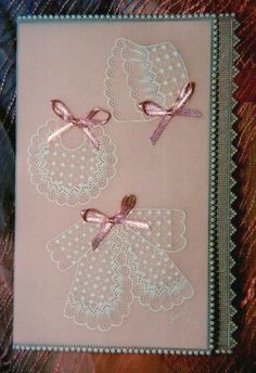 Delicate baby card with teeny pink layette set, for a newborn.