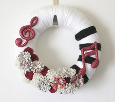I really LOVE this! If I had a room specifically for my piano and what not this would be in it!!  A 12-inch yarn and felt wreath with a music theme.    The base is a 12-inch straw wreath form, wrapped with thick white yarn; on the right side are five black yarn stripes representing piano keys. Two glittery red music note ornaments are attached to the top left and lower right, and between them are deep red and ivory colored handmade felt flowers, as well as some made from actual sheet music…
